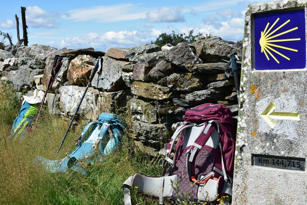 Mochilas de peregrinos y señal del Camino de Santiago